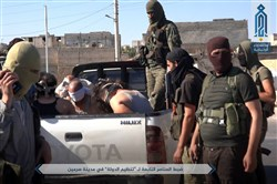 This July 9 photo — released by Ibaa news agency, the communications arm of the al-Qaida-linked Levant Liberation Committee, an outlet that is consistent with independent AP reporting — shows al-Qaida-linked fighters after they detained alleged members of the Islamic State group in the northwestern Syrian village of Sarmin in Idlib province.