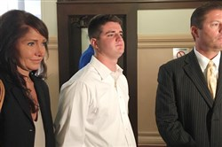 Former Chartiers Valley student and sports standout Ross Wilkerson is flanked by his attorneys, Michele and Michael Santicola, on Wednesday in the Allegheny County Courthouse after the district attorney's office announced it was dropping rape charges against Mr. Wilkerson.
