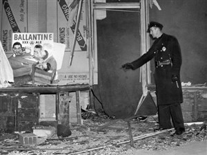 Police inspect Russell Golomb's bombed beer store. Three months prior, his father Ben's store was also attacked. Photo published Feb. 8, 1946.