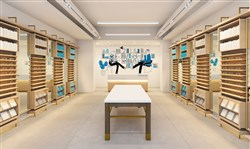"Warby Parker's East Liberty store is designed to look like ""an optical library,"" complete with light-oak shelves lined with eyewear, colorful book displays, rich brass detailing and a marble ""reference desk."""