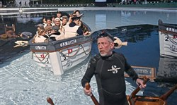 "Cast members of ""Unsinkable"" on a lifeboat are pushed toward ""the shore"" while producer D.C. Cohan pulls an overturned table out of the water as the sun rises over the Settler Cabin wave pool Tuesday morning."