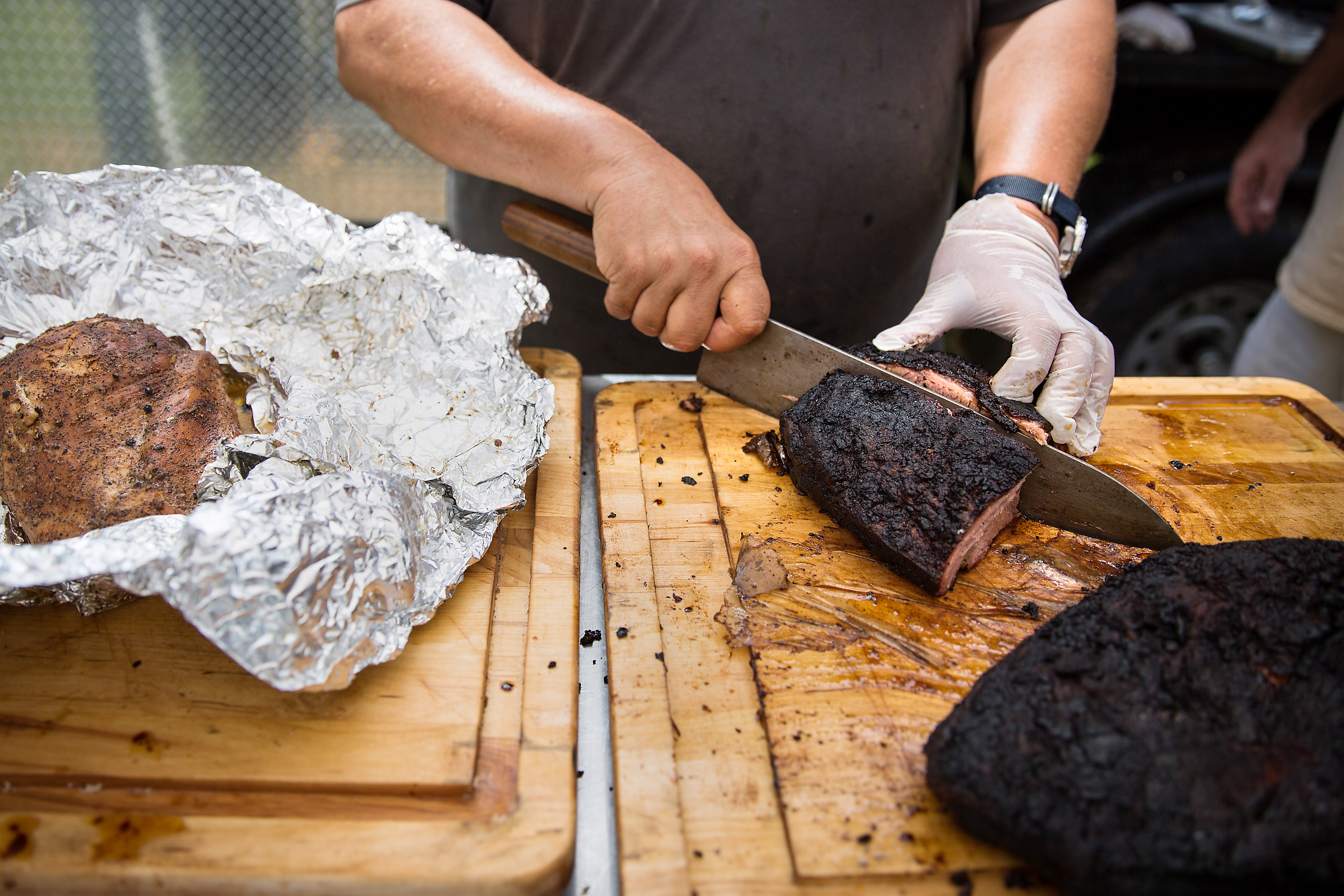 Spork Pit Chris Frangiadis cuts up a brisket during the opening of Spork Pit, a Texas-style BBQ pit next to Spork restaurant, which serves slow and low smoked meats in Garfield.