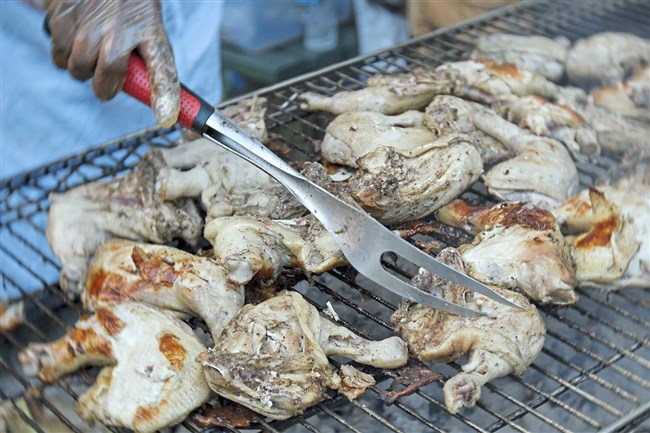 Chicken cooks over a grill at Jerk Fess, held in July in Highland Park. Organizer Steve Miller is gearing up for a similar festival, the Pittsburgh Caribbean Seafood Fess, this Sunday in Highland Park. Local restaurants will bring a variety of island seafood dishes.