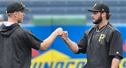 The Pirates' George Kontos fist bumps fellow pitcher Chad Kuhl during batting practice before taking on the Tigers Monday.