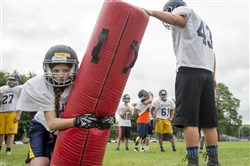 Shenango 10th-grade wide receiver Shayla Ettinger tackles a bag during the first padded preseason practice on Monday, Aug. 7, 2017 at Shenango High School.