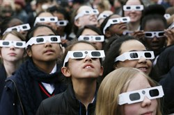 School children wearing protective glasses pose for photographers outside The Royal Observatory during a partial solar eclipse in Greenwich, south east London March 20, 2015.