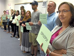 "At right, Michele Batiste, of the nonprofit Animal Friends, holds a sign labeled ""Epilepsy"" as the Mental Health First Aid class members explore their perceptions of the severity of various mental and physical illnesses."