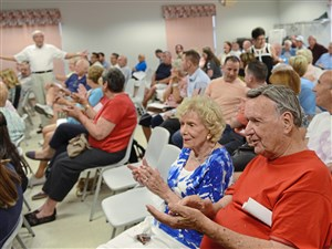 Marge Mueller, center, and her husband Bill Mueller, right, begin clapping as they wait for South Fayette board of commissioners to return from a recess taken at the beginning of meeting Wednesday, August 9, 2017, at the South Fayette Area Senior Citizens Center in South Fayette.