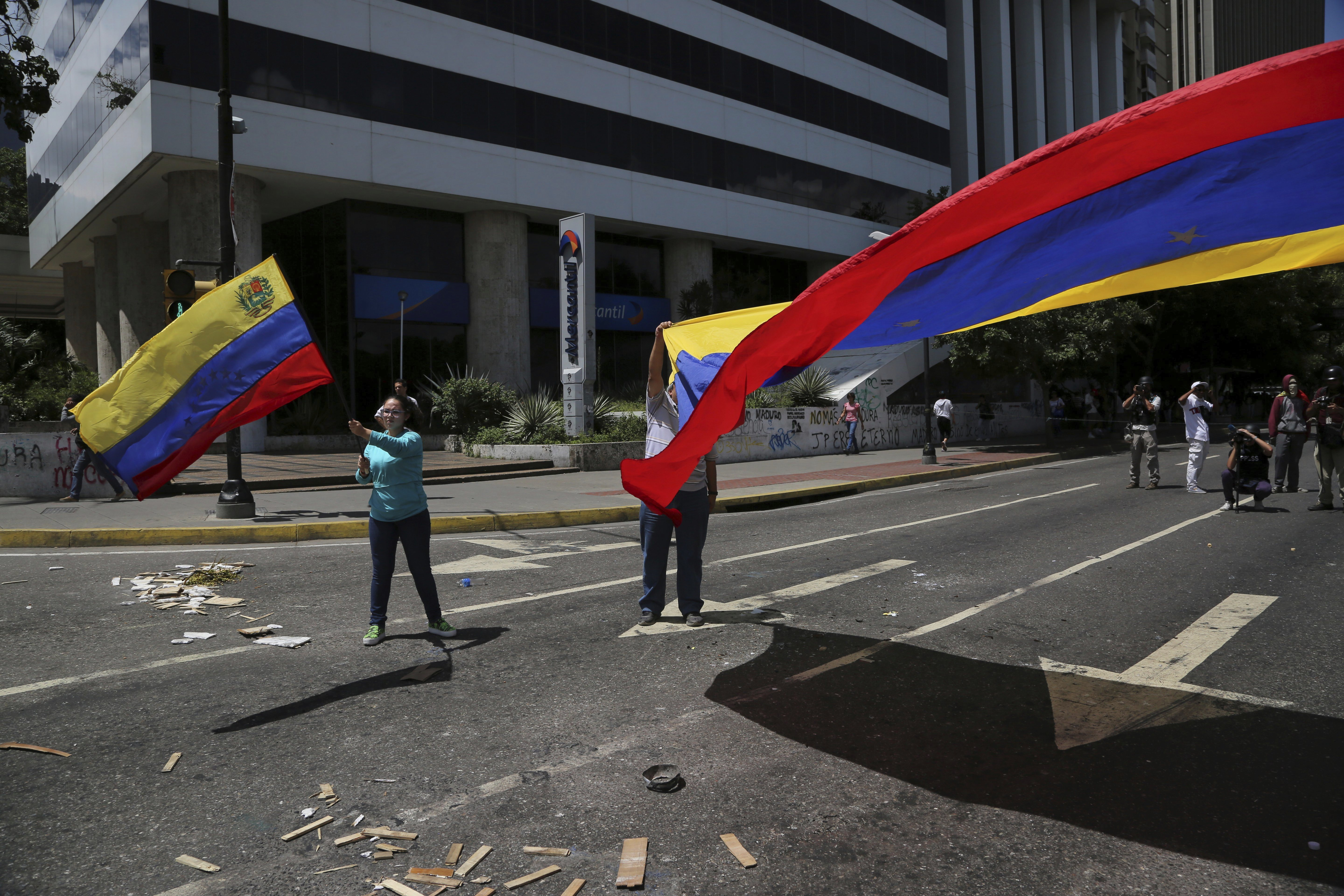 """Venezuela Political Crisis-2 Anti-government demonstrators wave Venezuelan national flags during a protest against Venezuela's President Nicolas Maduro in Caracas, Venezuela, Tuesday, Aug. 8, 2017. The U.S. State Department is repeating its rejection of the new government-loaded assembly rewriting Venezuela's constitution, saying it's """"an illegitimate product of a flawed process designed by a dictator."""" (AP Photo/Wil Riera)"""