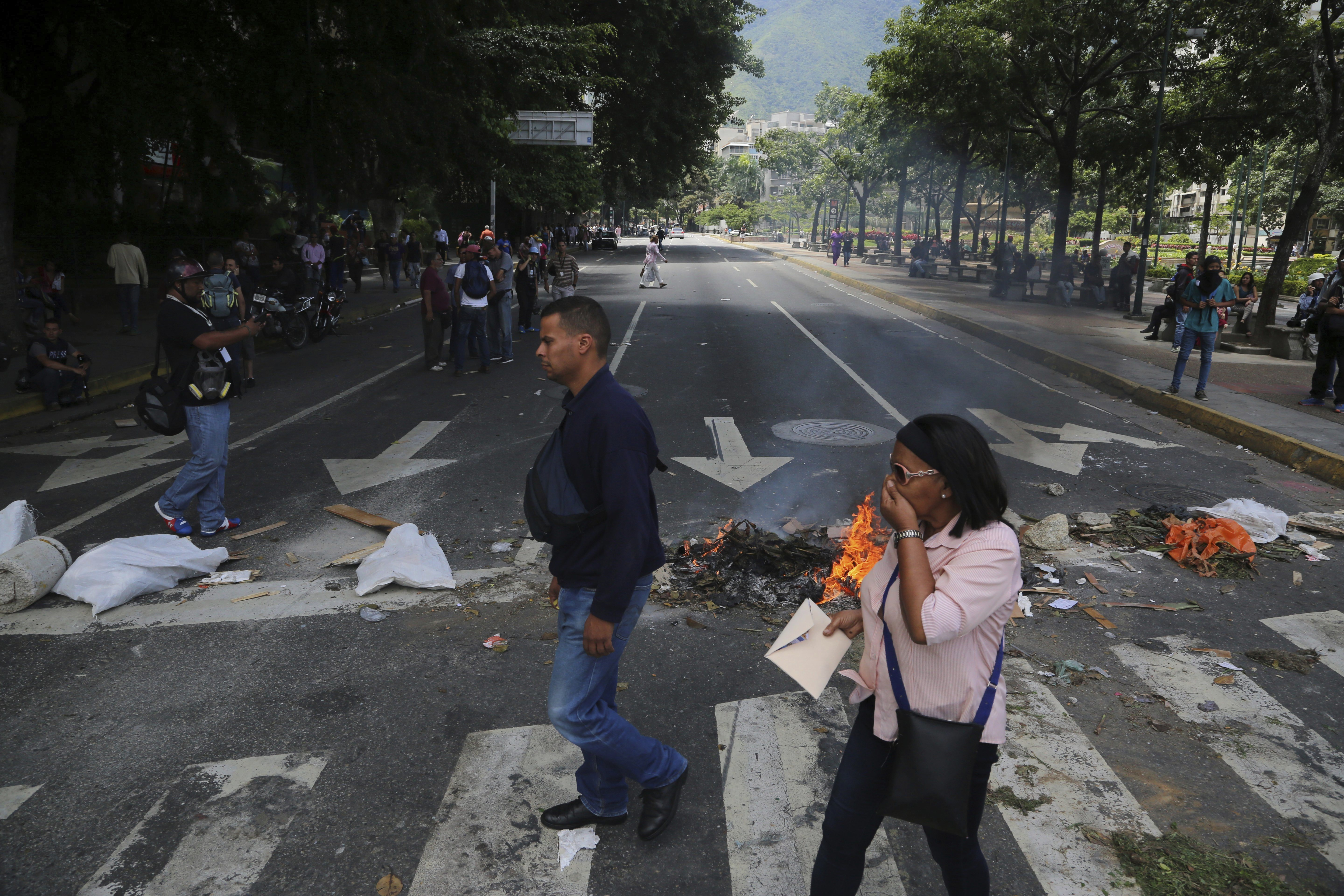 """Venezuela Political Crisis-3 Pedestrians walk past a barricade set up by anti-government demonstrators, in Caracas, Venezuela, Tuesday, Aug. 8, 2017. The U.S. State Department is repeating its rejection of the new government-loaded assembly rewriting Venezuela's constitution, saying it's """"an illegitimate product of a flawed process designed by a dictator."""" (AP Photo/Wil Riera)"""