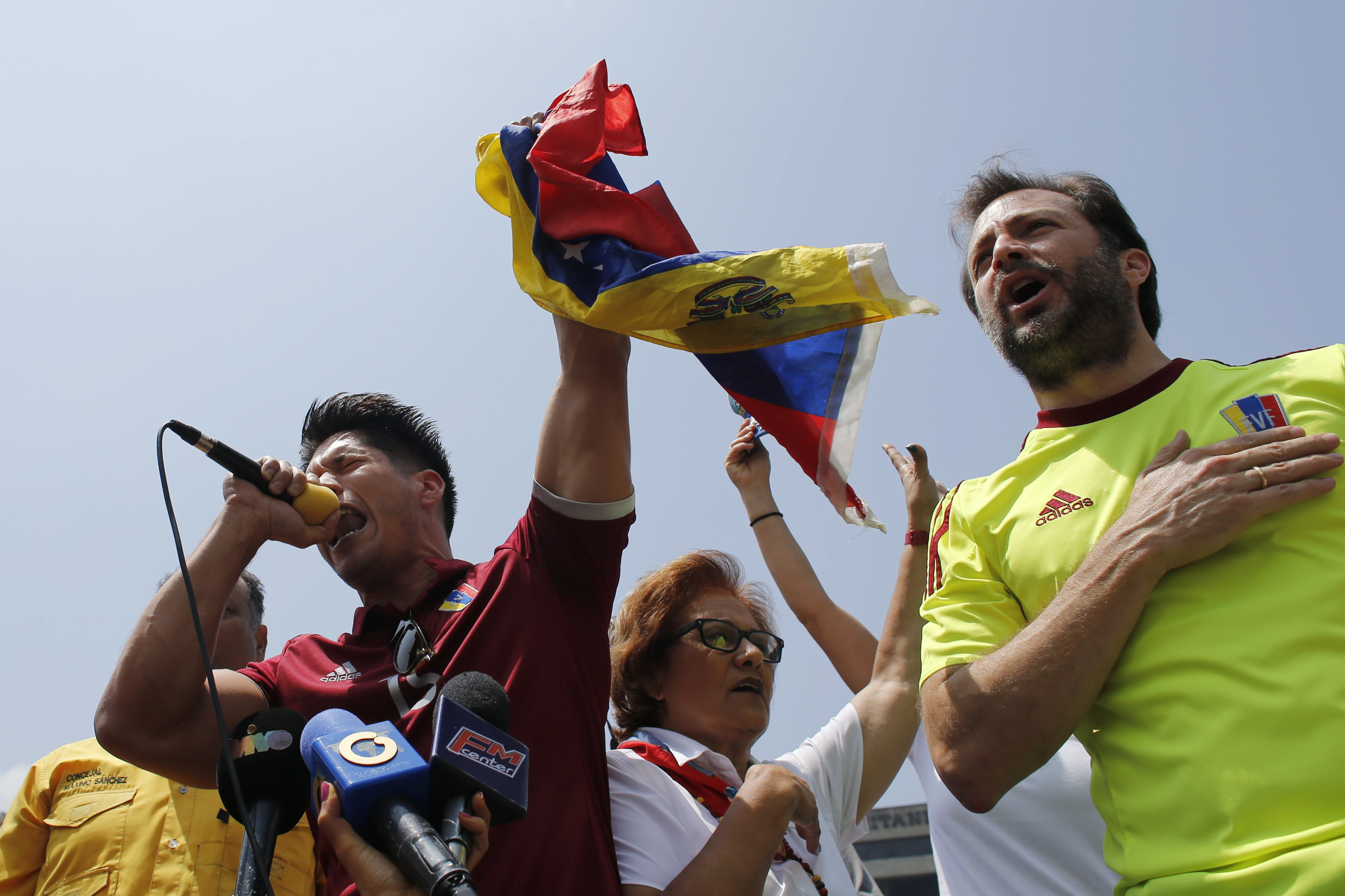 Venezuela Political Crisis-4 FILE - Venezuelan singer Jesus Alberto Miranda, known as Chino, left, and Chacao Mayor Ramon Muchacho, sing the national anthem during an anti-government protest in Caracas, Venezuela. Venezuela's supreme court ordered the removal and arrest of Muchacho, Tuesday, Aug. 8, 2017, for not following an order to remove barricades set up in the Chacao district of eastern Caracas. He's the fourth opposition mayor whose arrest the high court has sought in the past two weeks. (AP Photo/Ariana Cubillos, File)