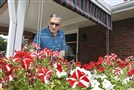 Joe Randig, a retired printer now 70, and a survivor of polio from the age of 5 years old, works on the flowers at his home.