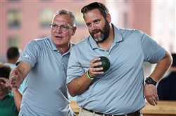 Tom Schachner, left, from Fox Chapel, and Ryan Sullivan, from Robinson Township, strategize before the next toss at the Heinz History Center's Eighth Annual Bocce Tournament and Festival on Saturday under the Veteran's Bridge overpass in the Strip District.