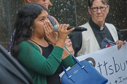 Fernanda Ruiz, 20, of Brookline wipes away tears while speaking to the audience at a protest in front of Sen. Pat Toomey's Downtown office on Tuesday. Ms. Ruiz is originally from Mexico. Her status in the U.S. would be threatened if the DACA program were cancelled.