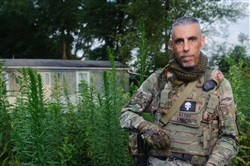 """Christian Yingling, 45, of New Derry dons his militia uniform on Monday. He is the leader of the Pennsylvania Lightfoot Militia, based out of Latrobe. The name """"Gypsy"""" on his uniform signifies his radio call name."""