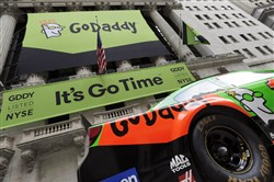 In this 2015 file photo, GoDaddy signage and a race car announce the company's IPO in front of the New York Stock Exchange in New York.