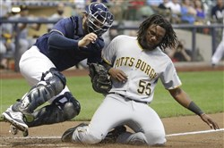 Brewers catcher Manny Pina tags out Pirates first baseman Josh Bell at home during the fourth inning Tuesday in Milwaukee.