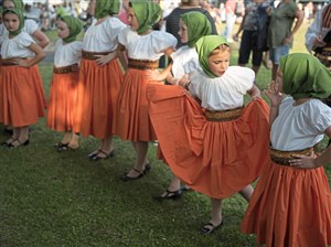 Adelina Simco, second from right, with the Trafford Junior Tamburitzans, plays with her skirt before a performance at the 58th Annual International Village on Tuesday at Renziehausen Park in McKeesport.