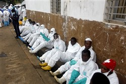 Burial team members rest outside an hospital in Freetown on Thursday.