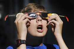 In this Wednesday photo, Colton Hammer tries out the new eclipse glasses he just bought from the Clark Planetarium in Salt Lake City in preparation for the eclipse.