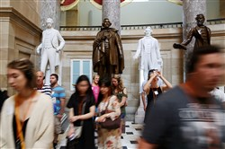 Tourists walk past a bronze statue of Confederate president Jefferson Davis that stands inside Statuary Hall at the U.S. Capitol on Thursday in Washington.