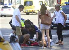 An injured person is treated in Barcelona, Spain, Thursday after a white van jumped the sidewalk in the historic Las Ramblas district, crashing into a summer crowd of residents and tourists. Several were killed or injured, police said.