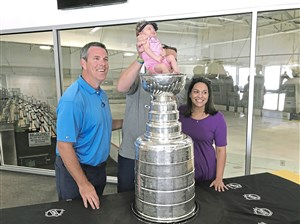 Paul and Jen Reissfelder of Plymouth, Mass., hoist their 12-day-old daughter, Evie, into the Stanley Cup as Penguins coach Mike Sullivan looks on Thursday at The Bog Ice Arena in Kingston, Mass.