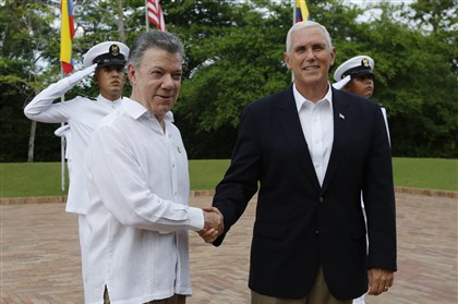 U.S. Vice President Mike Pence, right, is welcomed by Colombia's President Juan Manuel Santos at the presidential guesthouse in Cartagena, Colombia, Sunday.