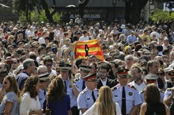 People holding a Catalan flag gather for a minute of silence in memory of the terrorist attacks victims in Las Ramblas, Barcelona, Spain, Friday.