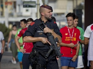 An armed policeman grimaces while on patrol in Cambrils, Spain, Friday.