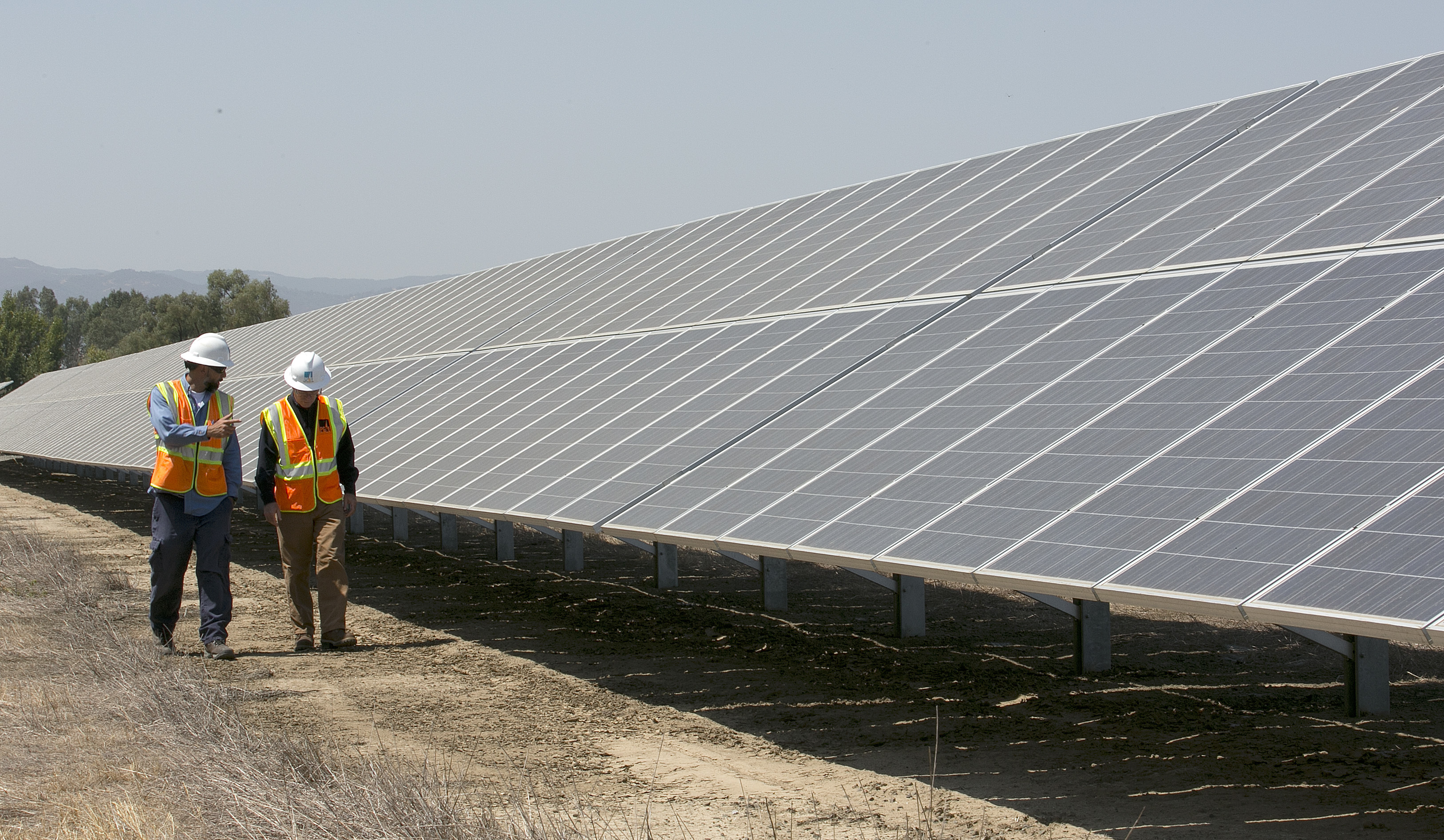 Eclipse Solar Energy-2 In this Thursday, Aug. 17, 2017 photo, Solar Tech Joshua Valdez, left, and Senior Plant ManagerTim Wisdom walk past solar panels at a Pacific Gas and Electric Solar Plant, in Dixon, Calif. Power grid managers say they've been preparing extensively for more than a year for this Monday's solar eclipse and that by ramping up other sources of power, mainly hydroelectric and natural gas, they are confident nobody will lose power or see a spike in energy prices. (AP Photo/Rich Pedroncelli)