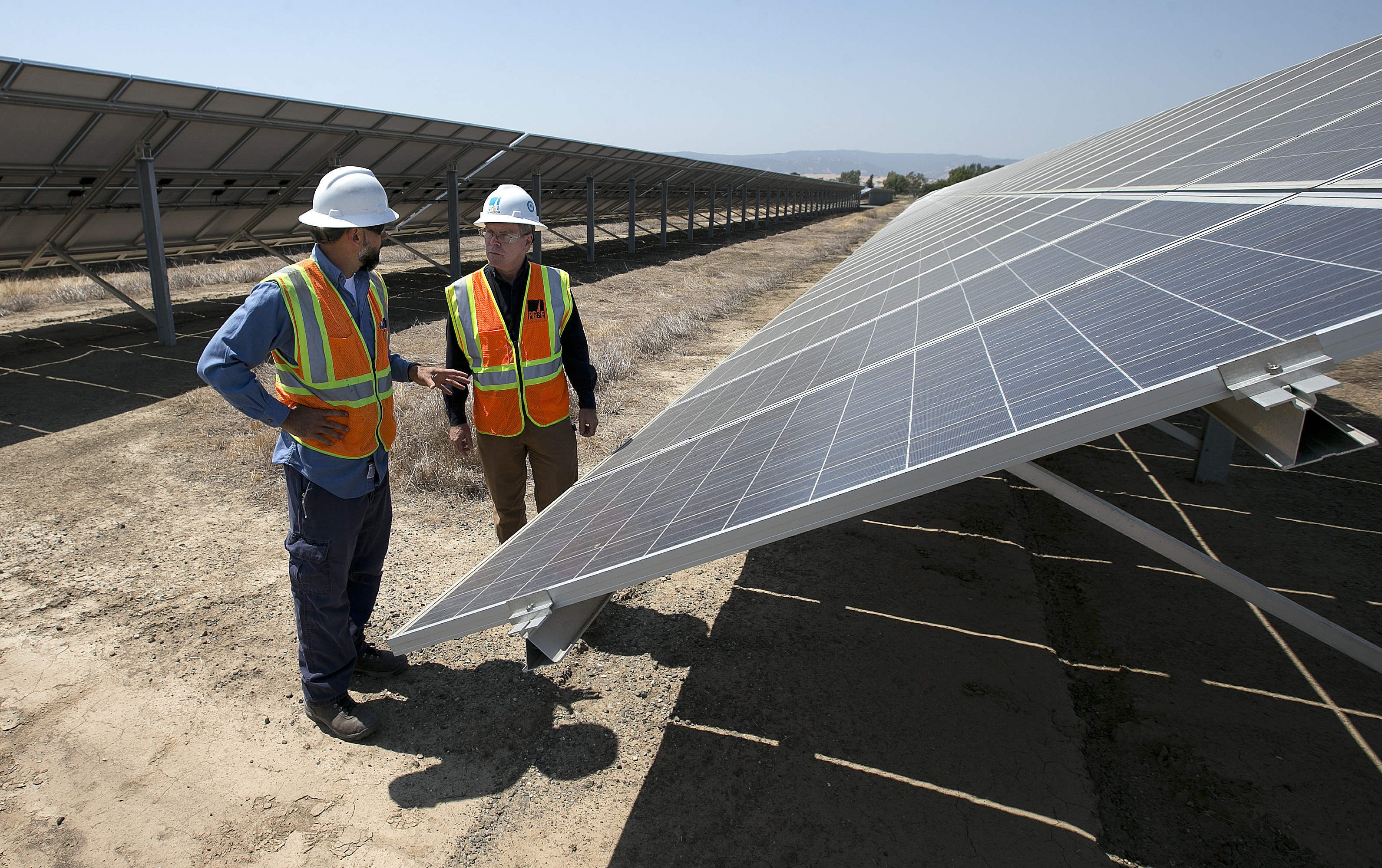 Eclipse Solar Energy-3 In this Thursday, Aug. 17, 2017 photo, Solar Tech Joshua Valdez, left, and Senior Plant Manager Tim Wisdom confer after a walk through of a Pacific Gas and Electric Solar Plant, in Dixon, Calif. Power grid managers say they've been preparing extensively for more than a year for this Monday's solar eclipse and that by ramping up other sources of power, mainly hydroelectric and natural gas, they are confident nobody will lose power or see a spike in energy prices. (AP Photo/Rich Pedroncelli)