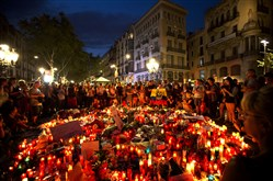 People gather Friday at a tribute of candles, flowers and messages to the victims of the attack on the historic Las Ramblas promenade in Barcelona, Spain.