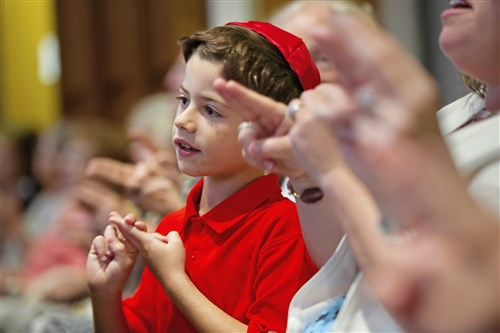 "Ari Padnos, 8, of Fox Chapel sings Shalom Aleichem, which means ""peace be upon you,"" during the Shabbat service at Temple Sinai in Squirrel Hill. The synagogue opened its Friday evening service to members of other faiths, including Christian and Muslim religious leaders."