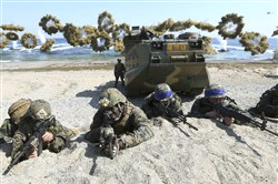 In this March 12, 2016, file photo, Marines of the U.S., left, and South Korea wearing blue headbands on their helmets, take positions after landing on a beach during the joint military combined amphibious exercise, called Ssangyong, part of the Key Resolve and Foal Eagle military exercises, in Pohang, South Korea.