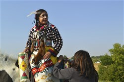 In this Aug. 18 photo, Julia Brien, left, prepares for the Crow Fair parade in Crow Agency, Mont.