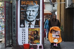 In this March 15 file photo, a man pushes a stroller past a magazine advertisement featuring President Donald Trump at a news stand in Shanghai.