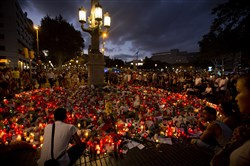 People stand next to candles and flowers placed on the ground Sunday in Barcelona, Spain, after terror attacks in the region of Catalonia that killed at least 14 people and wounded over 120.