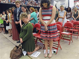 Ann Therese Lambo, right, Meredith Boone, kneeling, and more than 3,000 faculty, staff, students and their families celebrate Mass Sunday at Duquesne University's A.J. Palumbo Center. The annual Mass serves as the official start of the academic year at Duquesne University.
