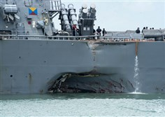 Damage to the portside is visible as the Guided-missile destroyer USS John S. McCain (DDG 56) steers towards Changi naval base in Singapore following a collision with the merchant vessel Alnic MC Monda.