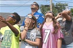 Scott Donnelly and members of his fifth-grade class view the partial eclipse Monday in front of Carnegie Elementary School in Carnegie.