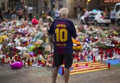 A man on Monday stands next to flags, flowers, messages and candles to the victims on Barcelona's historic Las Ramblas promenade on the Joan Miro mosaic, embedded in the pavement where the van stopped after killing at least 14 people in Barcelona, Spain.
