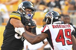 James Conner, left, breaks away from the Falcons' Deron Washington in the second half Sunday at Heinz Field.
