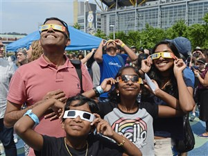 Paddy Sundararajan of Sewickley and his children, Sruti, Sritej and Swathi view the partial solar eclipse outside the Carnegie Science Center on the North Shore.