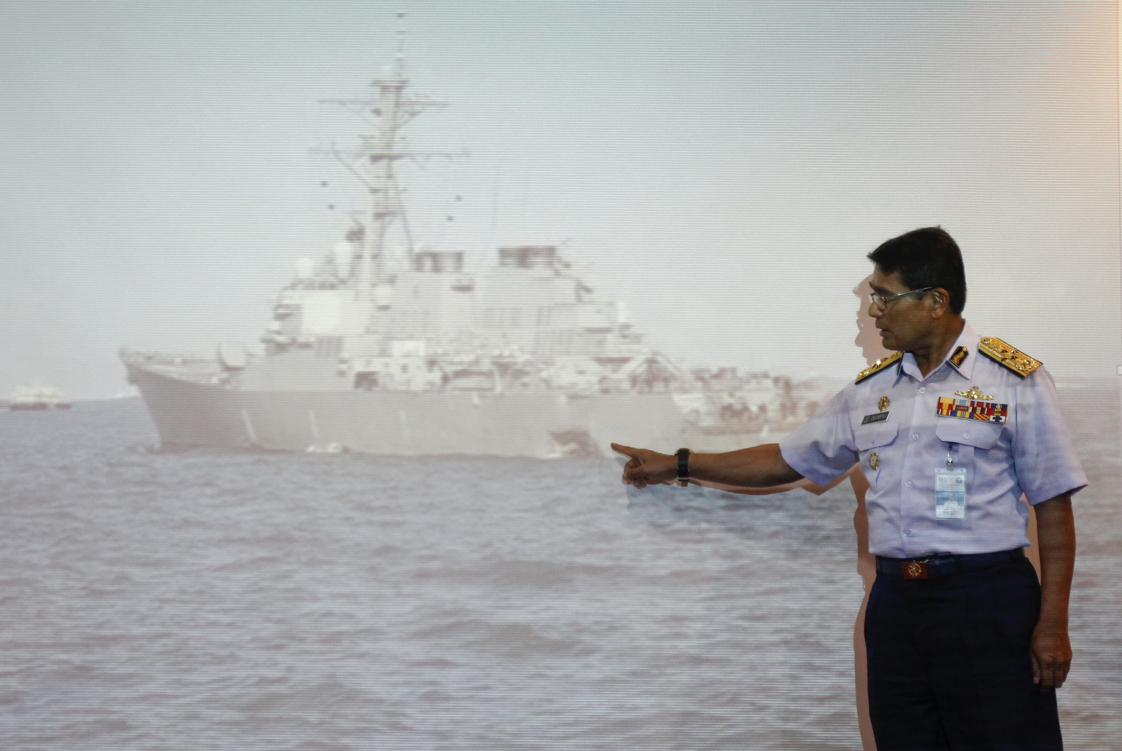 """APTOPIX Malaysia Singapore US Navy Ship Collision-1 Malaysian Maritime Director Indera Abu Bakar points the damage of USS John S. McCain shown on a screen during a press conference in Putrajaya, Malaysia, Monday, Aug. 21, 2017. The U.S. Navy said the USS John S. McCain arrived at Singapore's naval base with """"significant damage"""" to its hull after a collision early Monday between it and an oil tanker east of Singapore. A number of U.S. sailors are missing after the collision, the second accident involving a ship from the Navy's 7th Fleet in the Pacific in two months. (AP Photo/Daniel Chan)"""