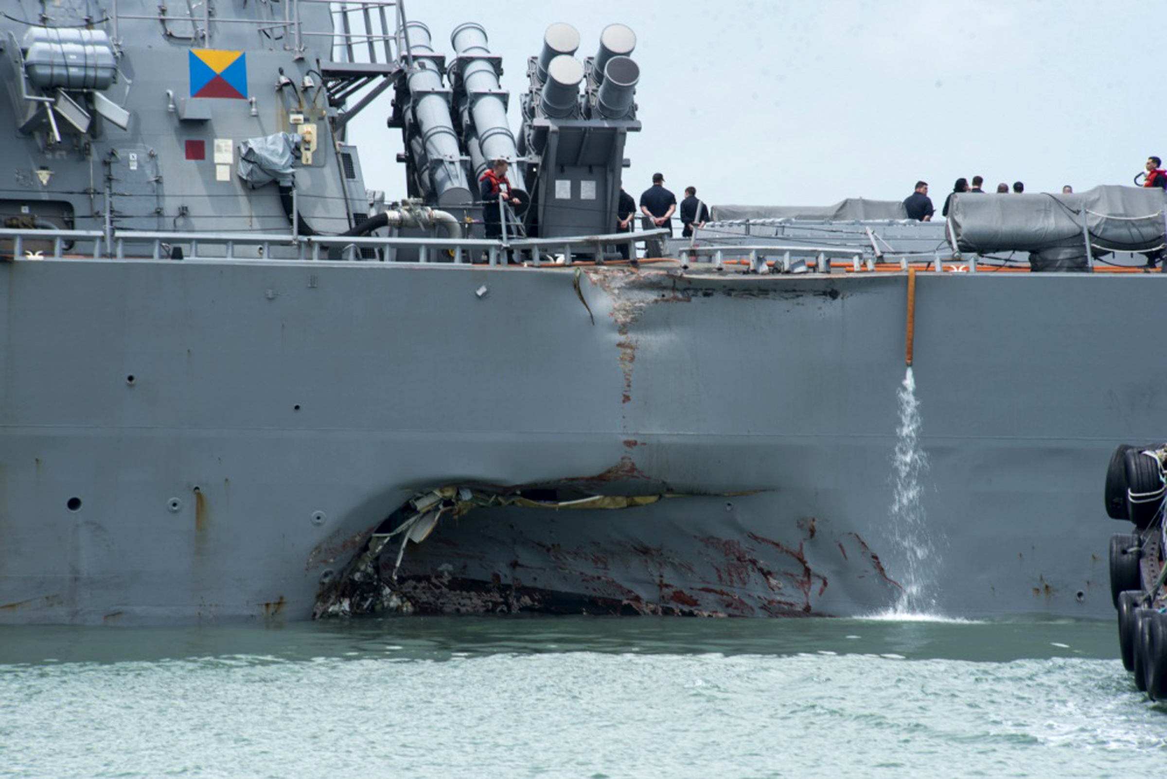"""APTOPIX Singapore US Navy Ship Collision Damage to the portside is visible as the Guided-missile destroyer USS John S. McCain (DDG 56) steers towards Changi naval base in Singapore following a collision with the merchant vessel Alnic MC Monday, Aug. 21, 2017. The USS John S. McCain was docked at Singapore's naval base with """"significant damage"""" to its hull after an early morning collision with the Alnic MC as vessels from several nations searched Monday for missing U.S. sailors. (Mass Communication Specialist 2nd Class Joshua Fulton/U.S. Navy photo via AP)"""