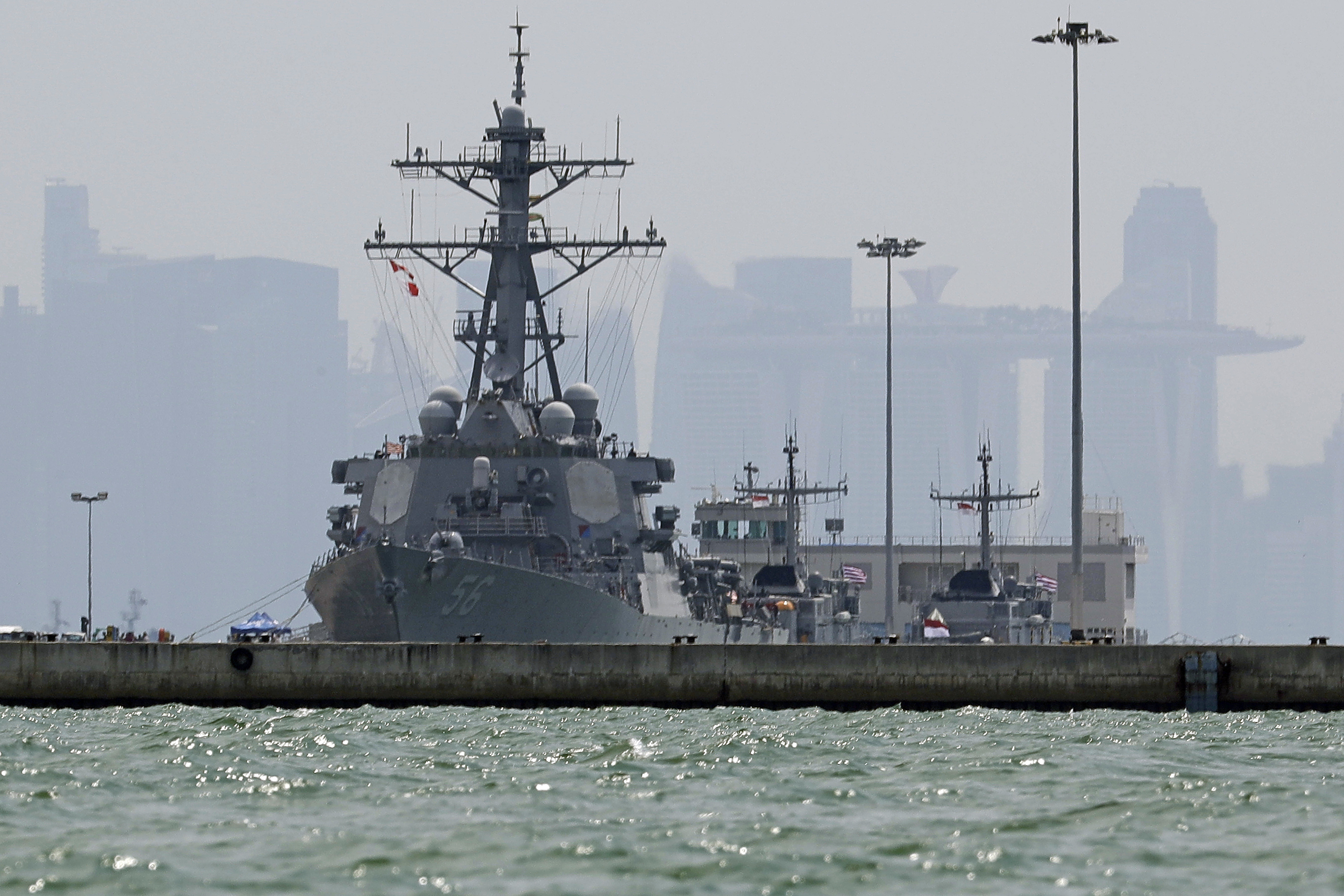 """Singapore US Navy Ship Collision-2 The USS John S. McCain is seen docked at Changi naval base after its accident on Monday, Aug. 21, 2017 in Singapore. The USS John S. McCain was docked at Singapore's naval base with """"significant damage"""" to its hull (blocked by berth) after an early morning collision with the oil tanker Alnic MC as vessels from several nations searched Monday for missing U.S. sailors. (AP Photo/Wong Maye-E)"""