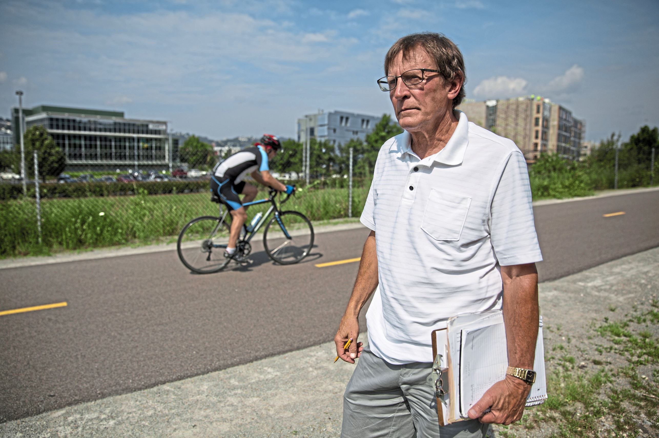 20170720adVolunteerCounter-01 Jerry Misiewicz of Bethel Park counts bikers and pedestrians as they pass by him along the Three Rivers Heritage Trail near the Hot Metal Bridge in South Oakland. It's just one of a number of volunteer efforts he's undertaken, from helping with tax returns to youth sports coach.