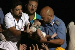 Rescuers on Tuesday pull out 7-month-old boy Pasquale from the rubble of a collapsed building in Casamicciola, on the island of Ischia, near Naples, Italy, a day after a 4.0-magnitude quake hit the Italian resort island.