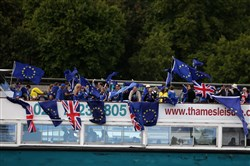 Members of the anti-Brexit campaign group The No 10 Vigil wave European Union and national flags as they sail up the Thames river from the Tower Millenium Pier in London on Saturday.